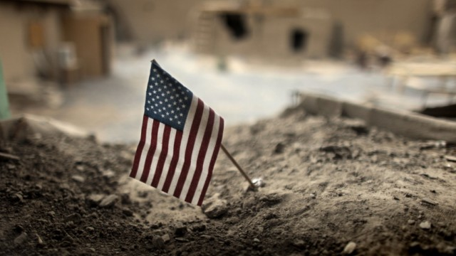 An American flag is placed in a dirt-filled barrier at Combat Outpost Nolen in the Arghandab Valley