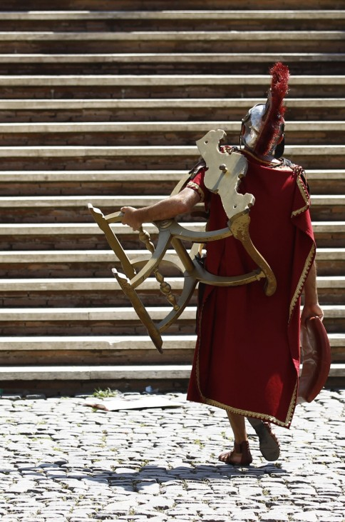A man dressed as a roman legionnaire leaves the Colosseum carrying a chair on a hot summer day in Rome