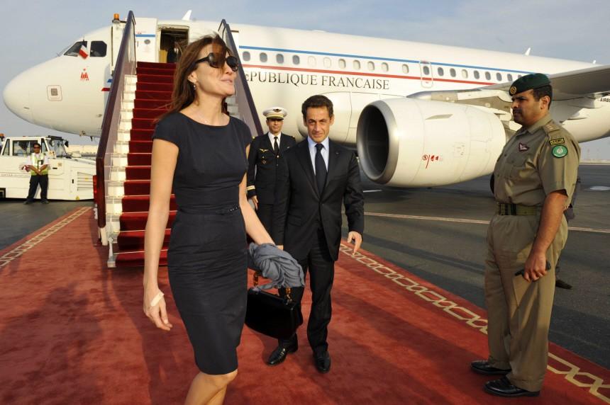 France's President Sarkozy walks with his wife Carla Bruni-Sarkozy at Doha airport