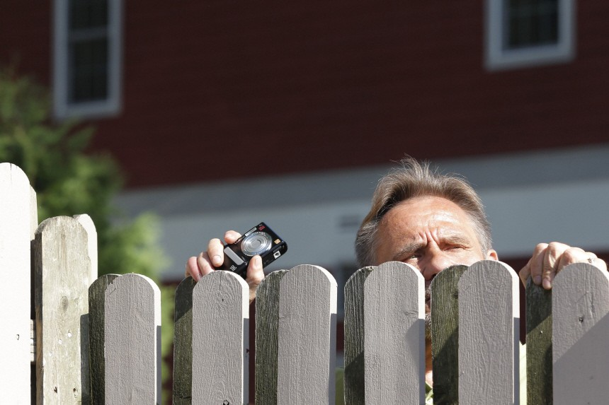 A spectator peeks over a fence as he tries to look at guests departing for Chelsea Clinton's wedding in Rhinebeck