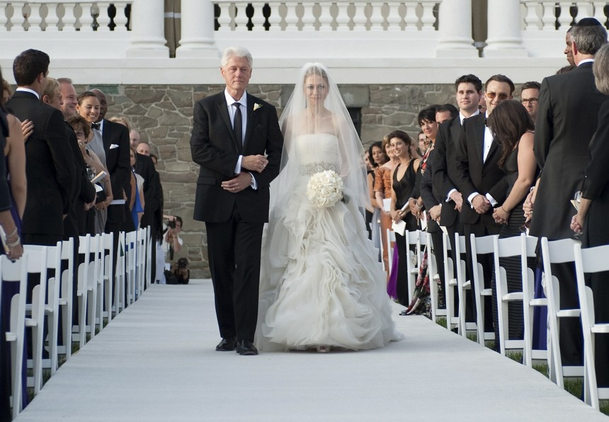 Former U.S. President Bill Clinton walks his daughter Chelsea Clinton down the aisle during her wedding at Astor Court in Rhinebeck