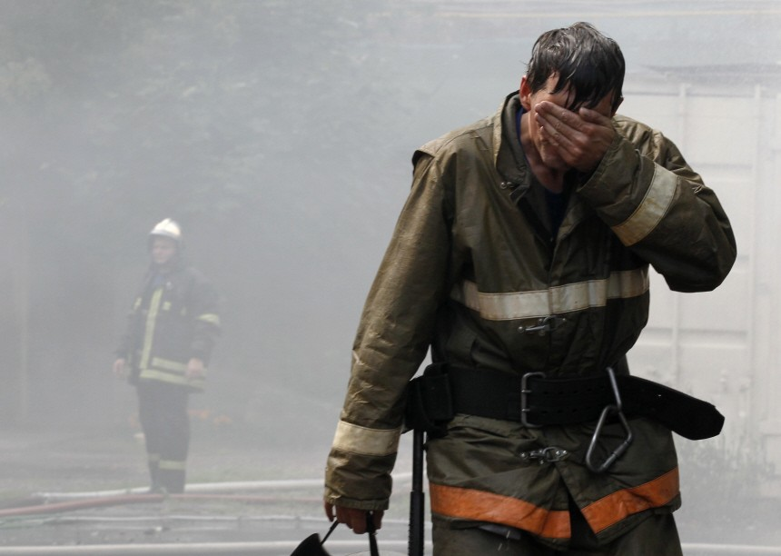 A firefighter wipes his face after extinguishing a fire at a Sunday school next to the Apostles Peter and Pavel church in Moscow