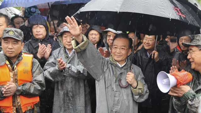 Chinese Premier Wen Jiabao waves to the crowd during his visit to the flooded town of Luozhen in Fuzhou