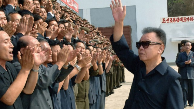 North Korean leader Kim Jong-il waves as North Korean workers applaud his visit to a construction site of the Kumyagang Army-People Power Station in North Korea in this picture released by North Korea's KCNA news agency