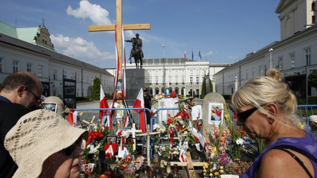 Supporters of late Polish President Lech Kaczynski gather at a wooden cross in front of the Presidential Palace in Warsaw