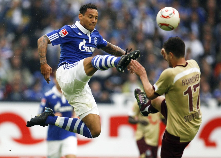 Schalke's Jones and Hanover 96's Stoppelkamp jump for a ball during the German Bundesliga soccer match in Gelsenkirchen