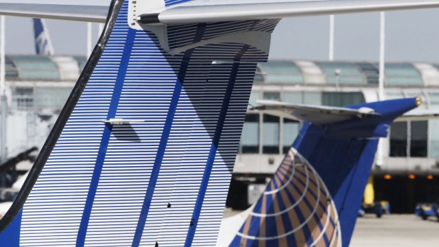 A Continental Airlines plane passes a United Airlines plane in Chicago