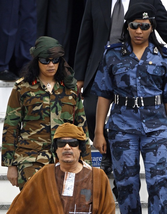Libyan leader Muammar Gaddafi walks down the stairs of his private airplane followed by his bodyguards at the Ciampino airport in Rome