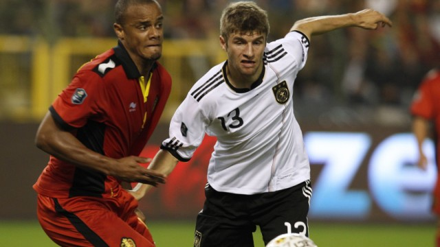 Belgium's Kompany fights for the ball with Germany's Muller during their Euro 2012 qualifying soccer match at the King Baudouin stadium in Brussels