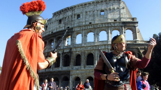 TWO MEN DRESSED AS ROMAN GLADIATORS WAIT TO POSE FOR TOURISTS IN FRONT OF THE COLOSSEUM IN ROME