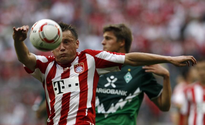 Bayern Munich's Olic is challenged by Werder Bremen's Proedl during German Bundesliga soccer match in Munich