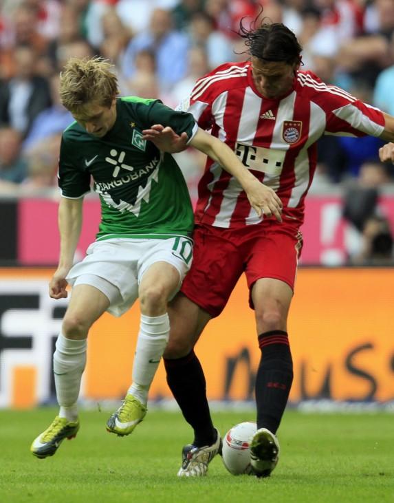 Werder Bremen's Marin is tackled by Bayern Munich's van Buyten during their German first division Bundesliga soccer match in Munich